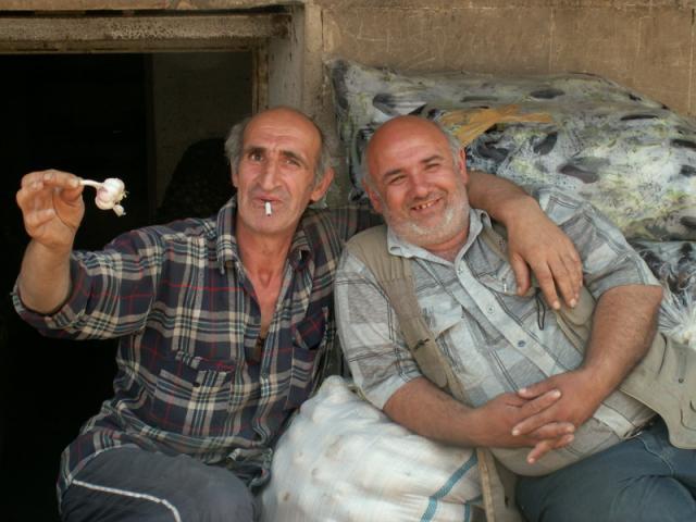 Veselí pánové prodávající česnek na tržišti v Kutaisi, Gruzie