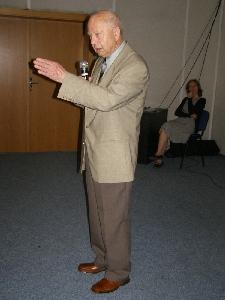 Vladimír Sellner přednáší, v pozadí dobrovolnice s PC
