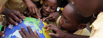 Děti si na globu ukazují země během hodiny v sirotčinci v haitském městě Jacmel. Ilustrační foto: UNICEF Canada