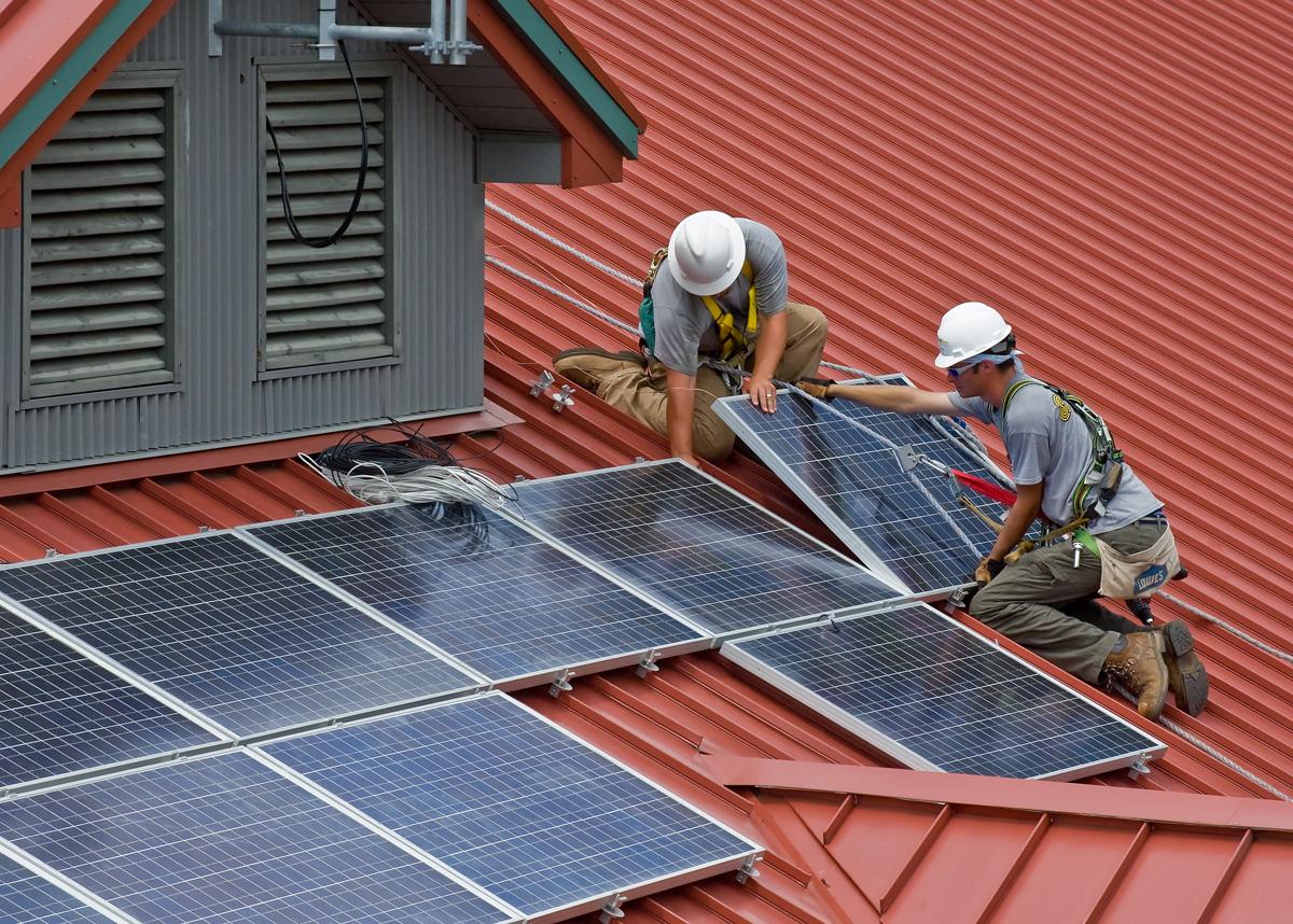 Instalace fotovoltaických panelů na střechu domu.