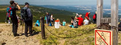 Turisté odpočívající na Sněžce mimo vyznačená místa před umístěním plotu